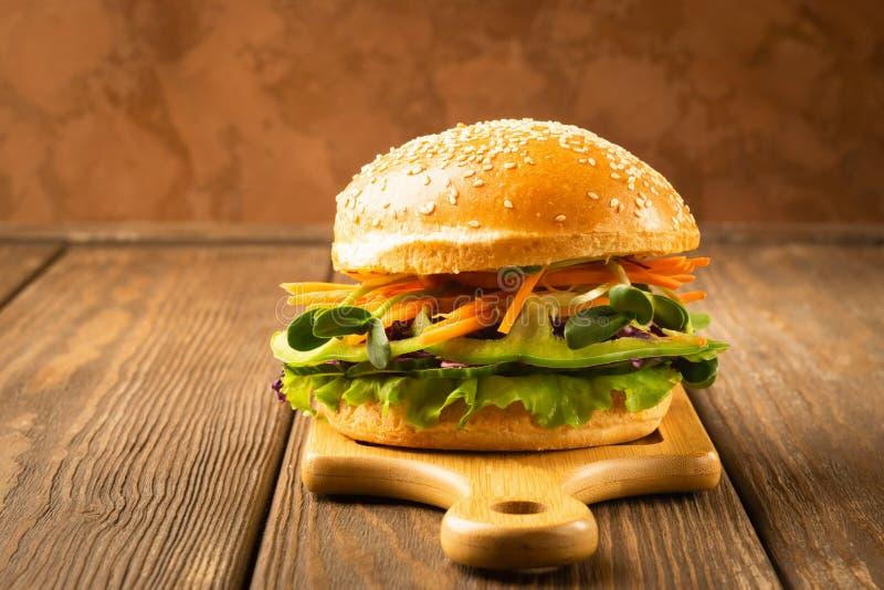 Hamburger della verdura dai verdi freschi del vegetablesand contro fondo scuro L'alimento sano di verdure di concetto Copi lo spa fotografia stock