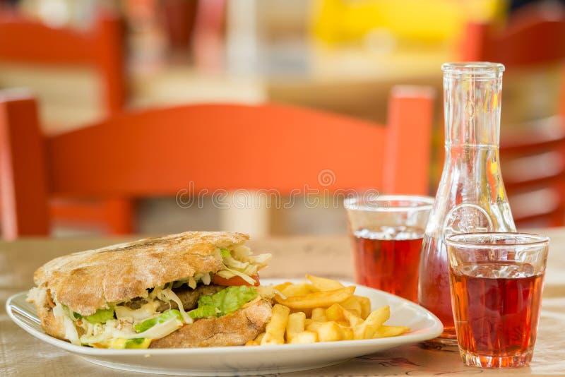 Hamburger des italienischen Brotes mit einem großen Steak Grafin und zwei Gläser Wein In der Taverne in Griechenland stockbilder