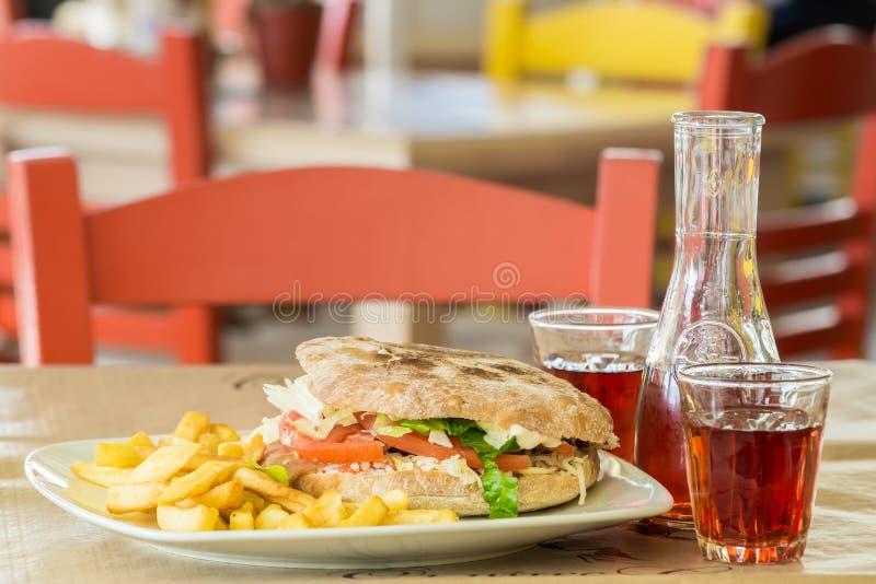 Hamburger des italienischen Brotes mit einem großen Steak Grafin und zwei Gläser Wein In der Taverne in Griechenland stockfotos
