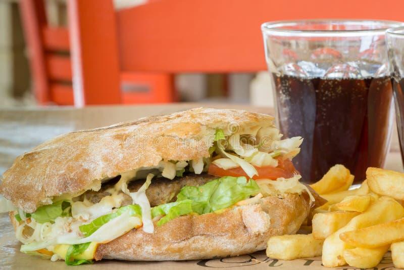 Hamburger des italienischen Brotes mit einem großen Steak und ein Glas des Getränks In der Taverne in Griechenland stockfotografie