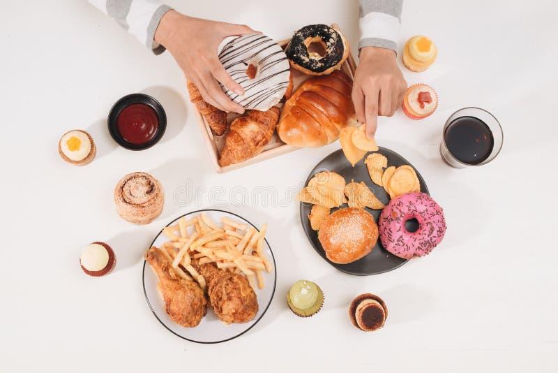 Hamburger di caloria con le patate fritte, la gente che mangia alla tavola del caffè, pranzo non sano fotografia stock libera da diritti
