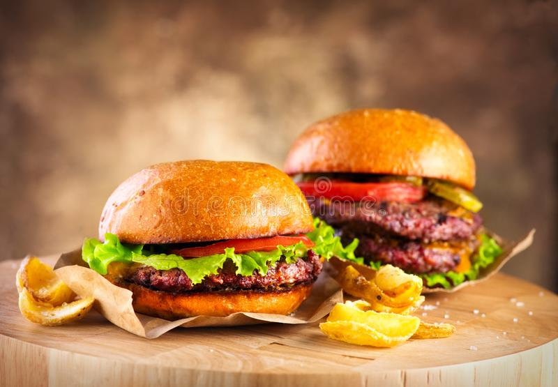 Hamburger and Double Cheeseburger with fries rotated on wooden table background. Cheeseburgers on fresh buns with succulent beef. And fresh salad ingredients stock images