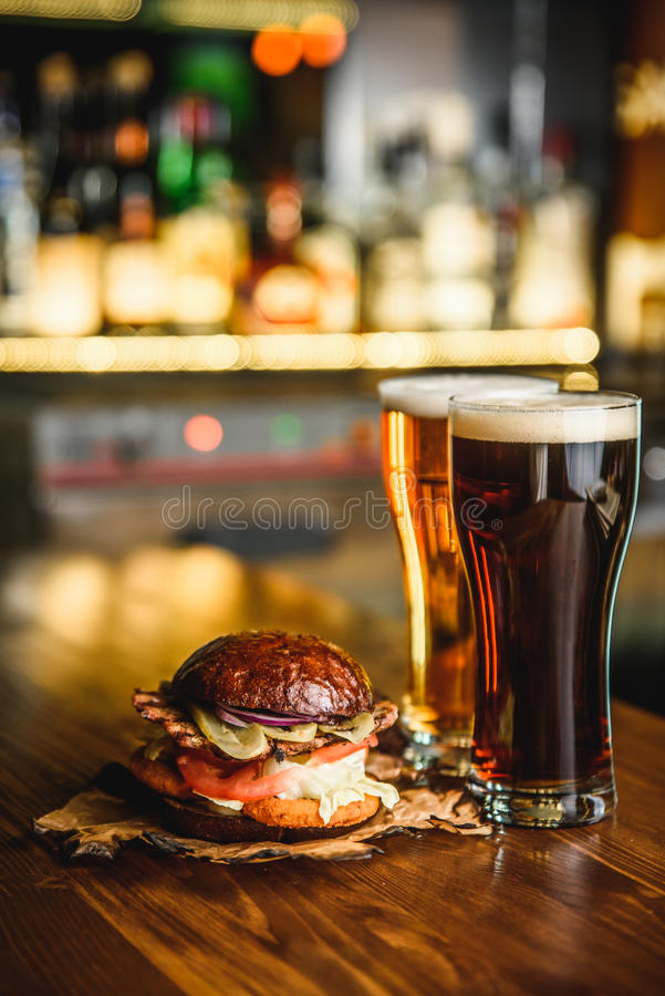 Hamburger e birra leggera scura su un fondo del pub fotografie stock libere da diritti