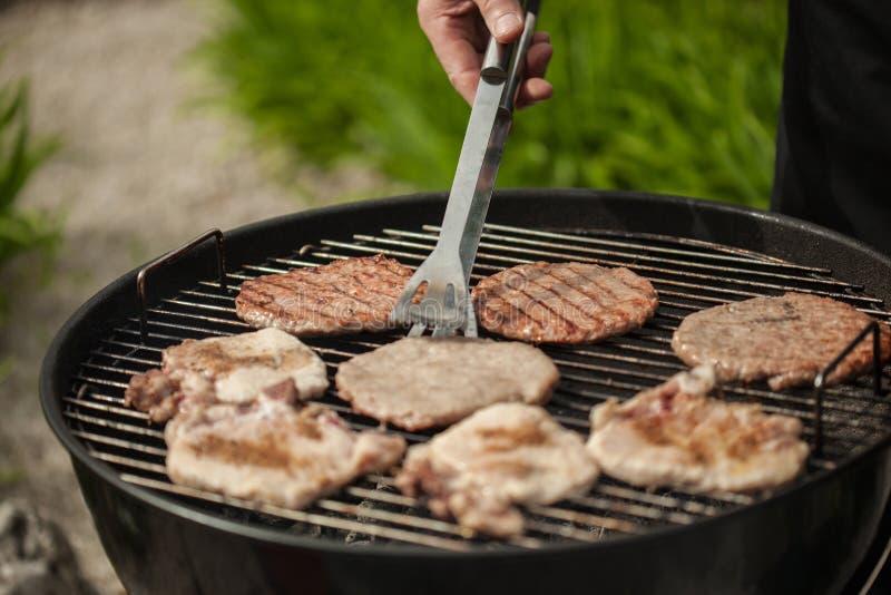Hamburger e bistecche di tornitura sulla griglia del Bbq fotografia stock