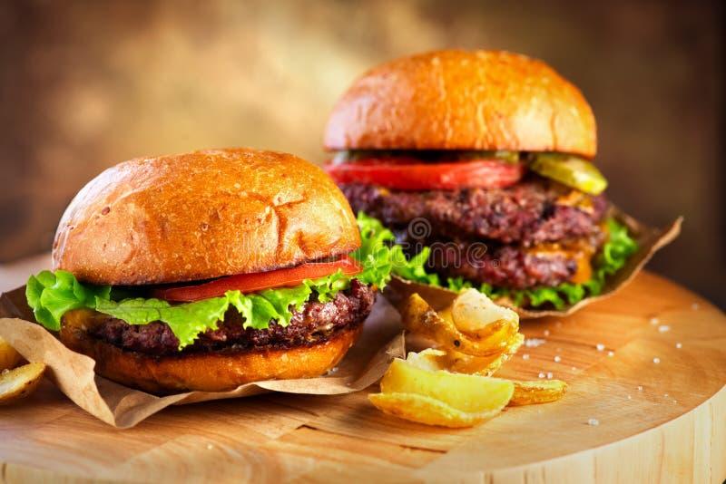 Hamburger e cheeseburger dobro com fundo de madeira da tabela das fritadas Cheeseburgers em bolos frescos com carne suculento foto de stock royalty free