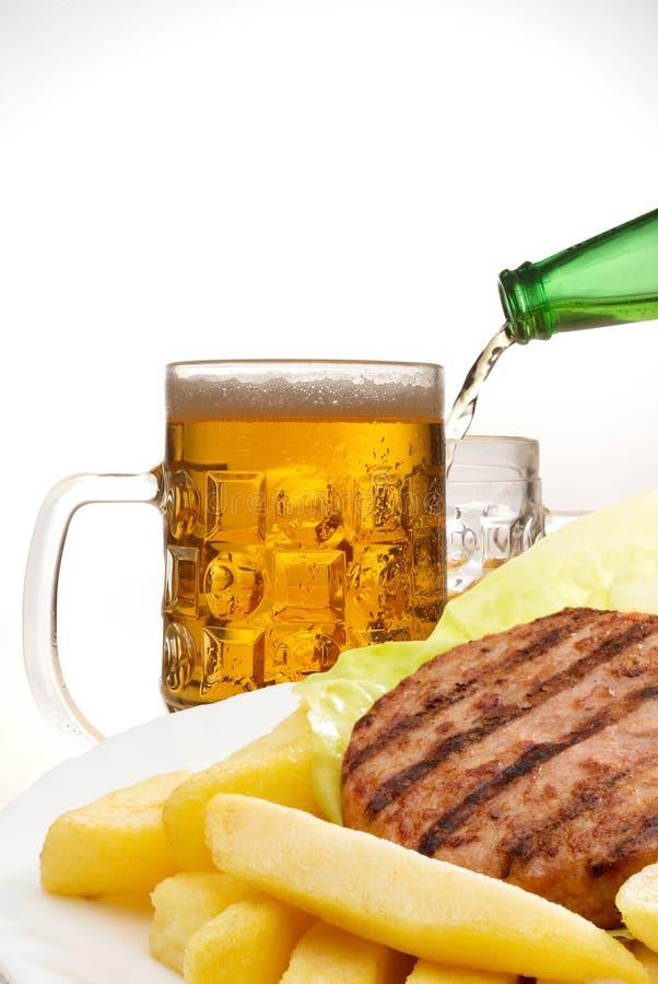 Hamburger e microplaquetas com cerveja fotografia de stock