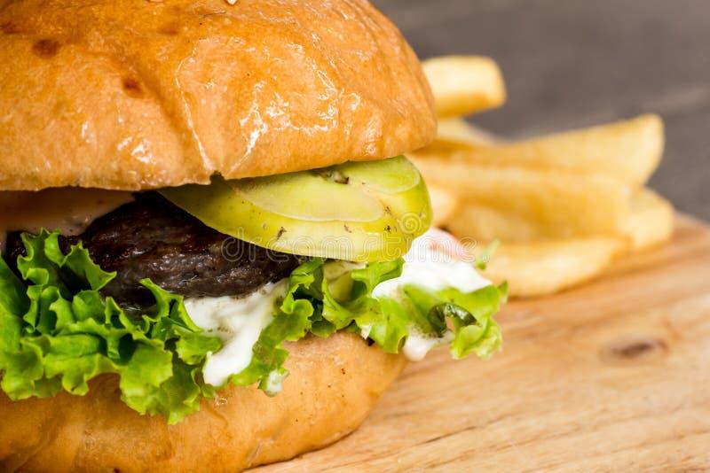 Hamburger e patate fritte sul legno immagini stock libere da diritti