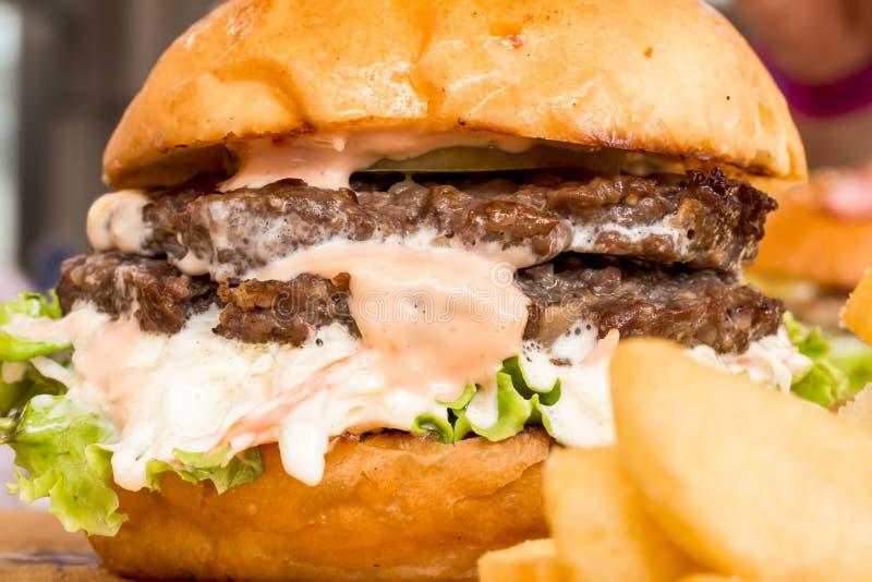 Hamburger e patate fritte sul legno immagini stock