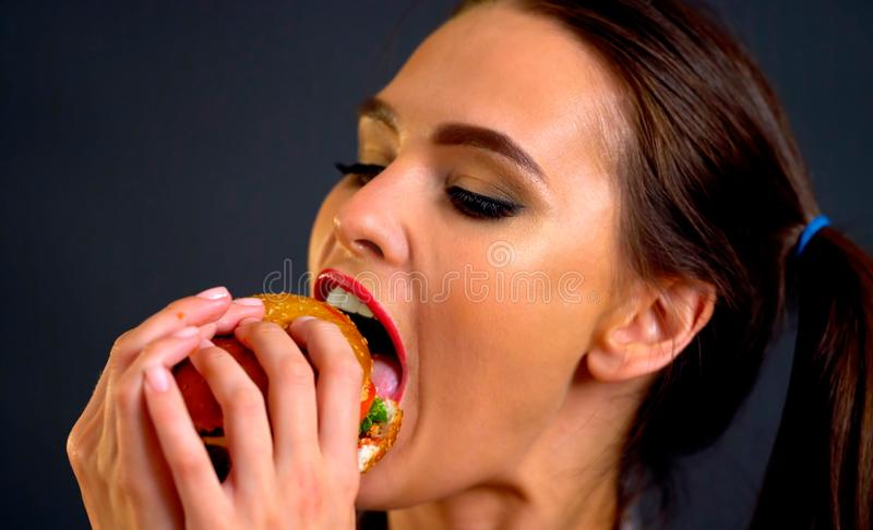 Hamburger eating contest. Woman eat with appetite . royalty free stock photography