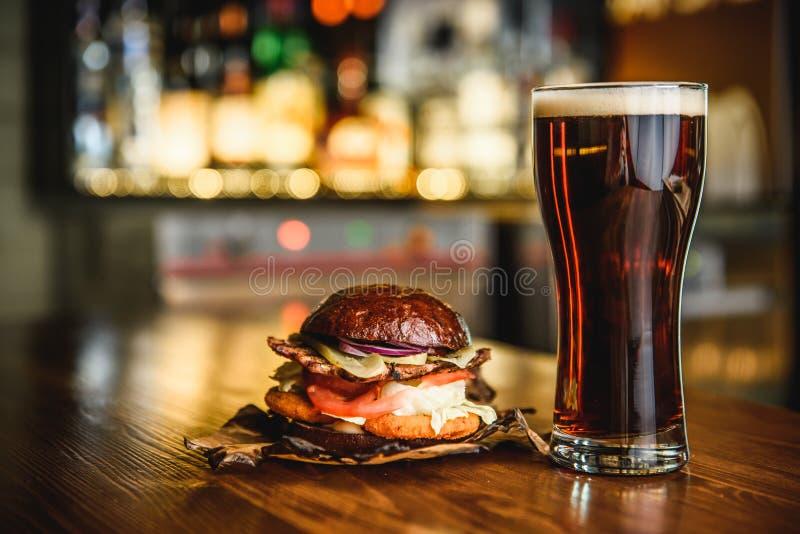Hamburger en donker bier op een barachtergrond stock afbeeldingen