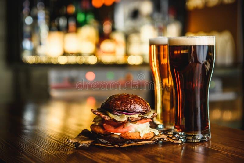 Hamburger en donker licht bier op een barachtergrond royalty-vrije stock afbeeldingen