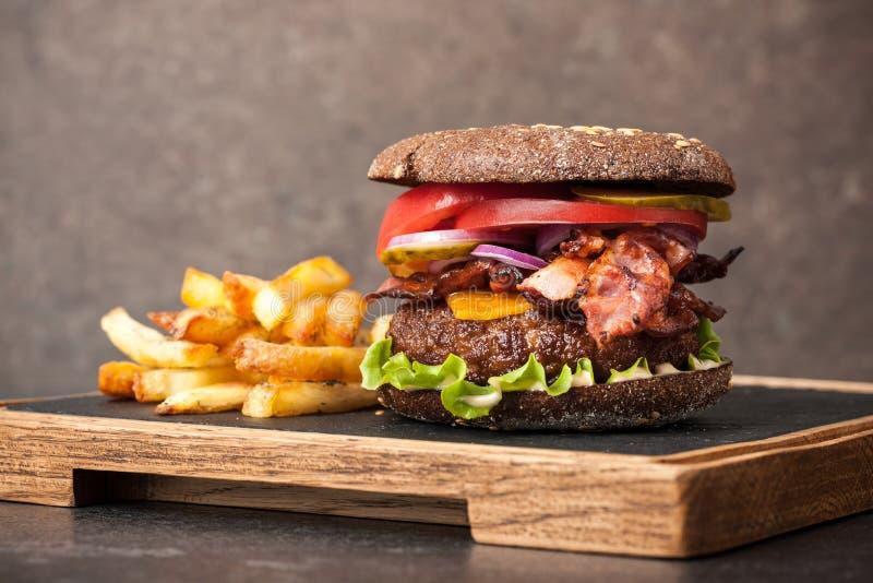 Hamburger en frieten bij het dienen van raad stock afbeelding