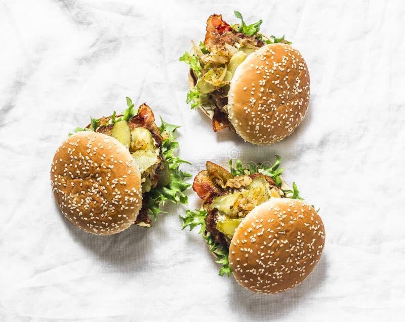 Hamburger fait maison classique avec la côtelette de porc, le lard, les conserves au vinaigre, les oignons frits et la sauce à mo photo libre de droits