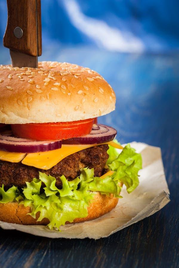 Hamburger fixado com faca imagem de stock royalty free