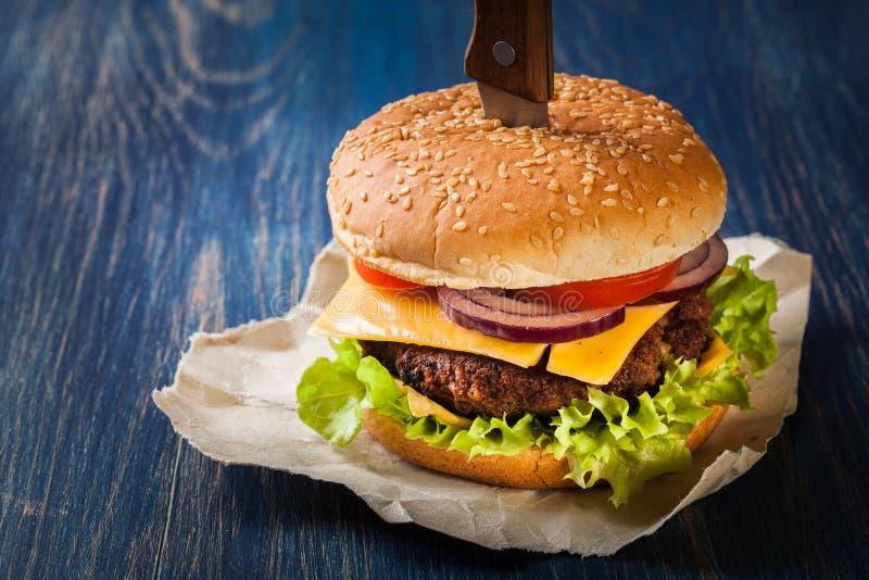 Hamburger fixado com faca imagem de stock