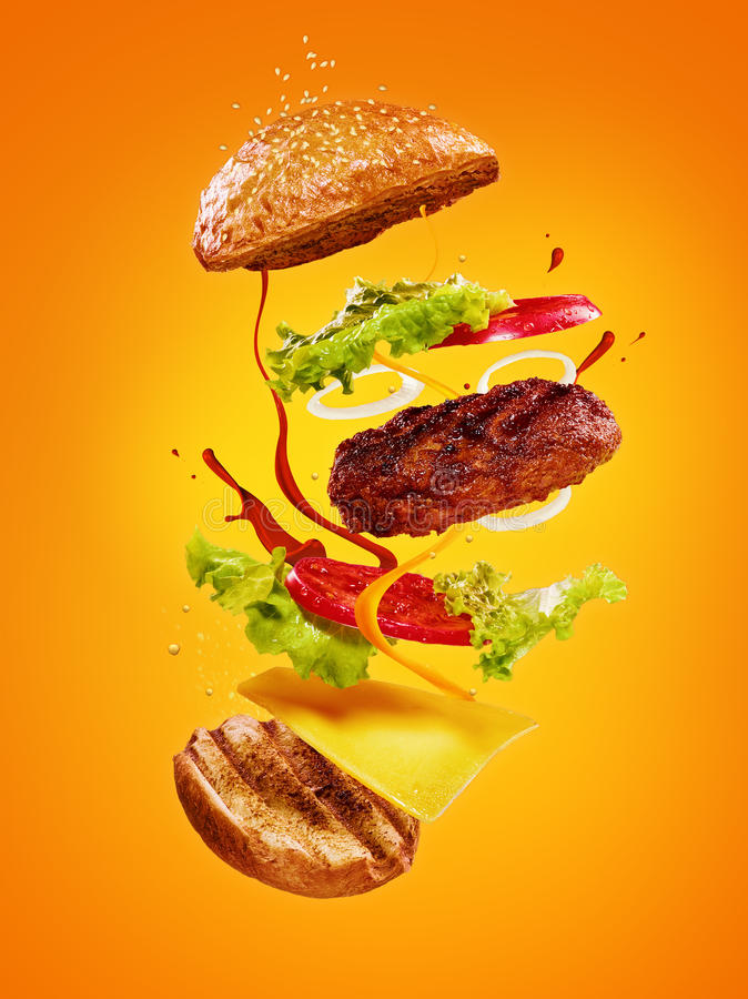 The hamburger with flying ingredients on orange background stock photos