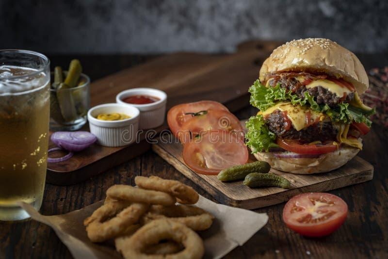 Hamburger frais et juteux Hamburger de fromage avec du boeuf ou lard, tomate de petit p?t?, anneau d'oignon et eau ou bi?re de sc images stock