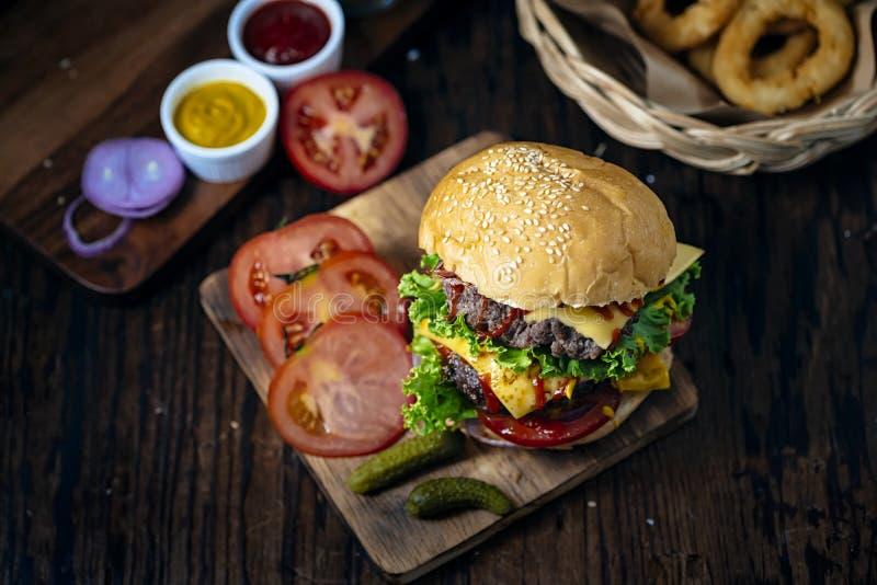 Hamburger fresco e suculento Hamburguer do queijo com carne ou bacon, tomate do rissol, anel de cebola e molho ou ketchup de toma foto de stock royalty free