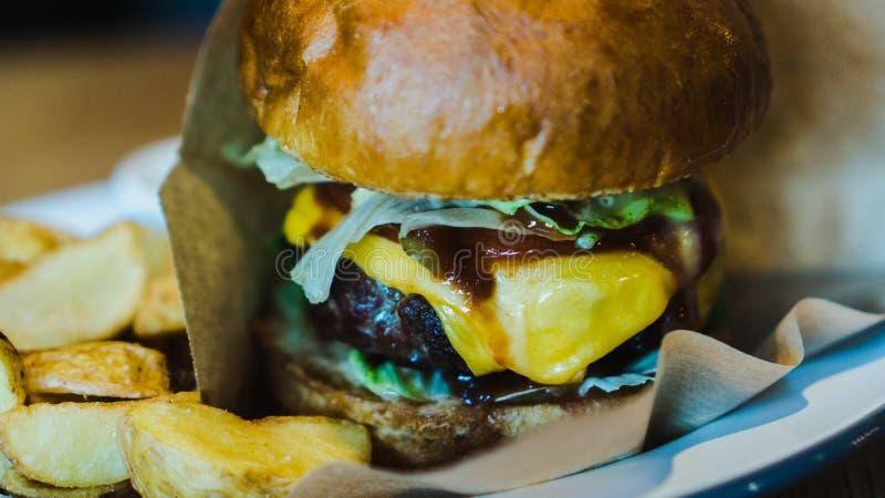 Hamburger fresco, saboroso, suculento com queijo, tomates, carne marmoreada temperado, salada fresca e batatas em uma tabela de m imagens de stock royalty free