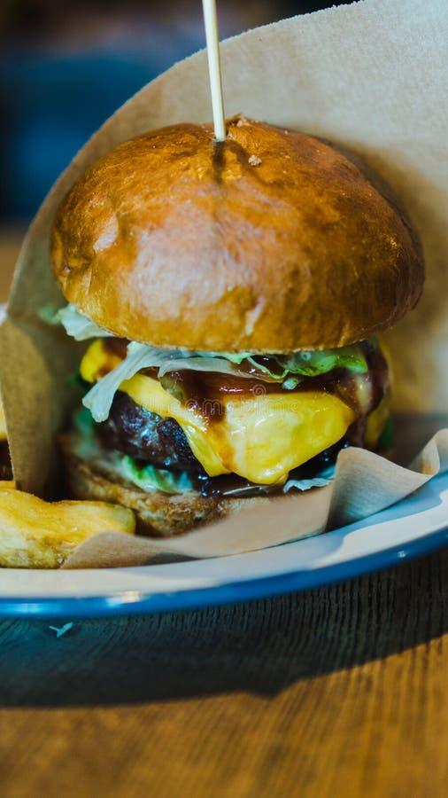 Hamburger fresco, saboroso, suculento com queijo, tomates, carne marmoreada temperado, salada fresca e batatas em uma tabela de m foto de stock