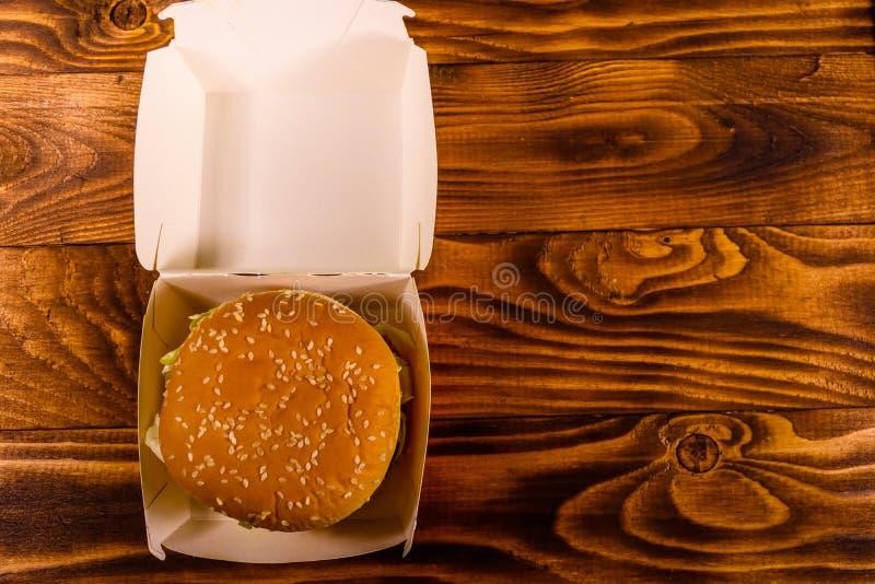 Hamburger fresco in scatola di carta sulla tavola di legno rustica la cima rivaleggia fotografia stock