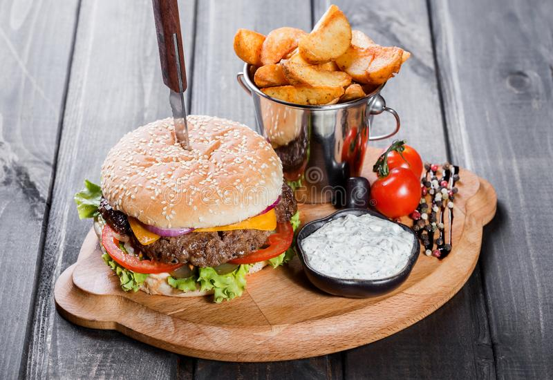Hamburger with fresh vegetables, cheese, sauce and fries on cutting board on dark wooden background. stock image