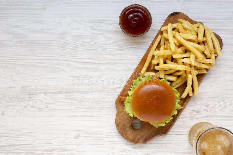 Hamburger, frieten, bbq saus en glas koud bier op een witte houten achtergrond, hoogste mening Lucht, vlak leg hierboven, van royalty-vrije stock afbeeldingen