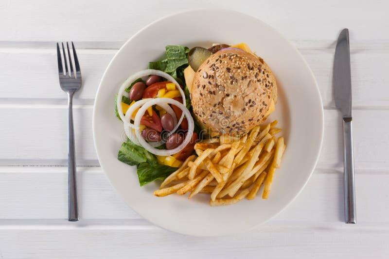 Hamburger, frieten, en salade in plaat op houten lijst royalty-vrije stock afbeelding