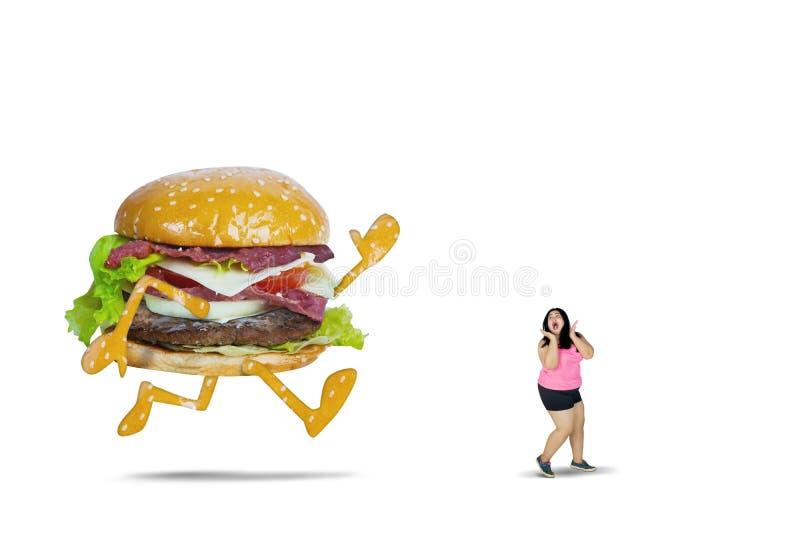 Hamburger grande que persegue a mulher gorda no estúdio foto de stock
