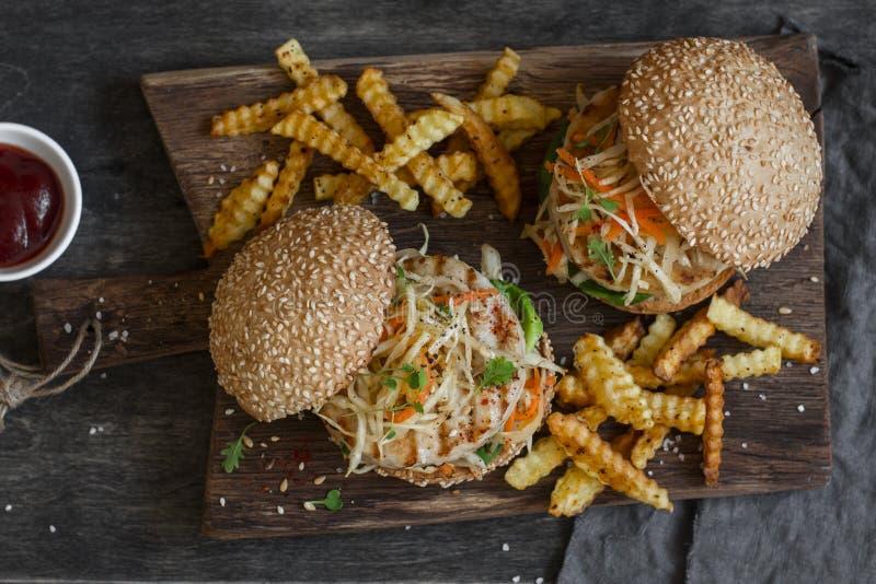 Hamburger grelhados da galinha e da salada de repolho em uma placa de madeira fotos de stock royalty free
