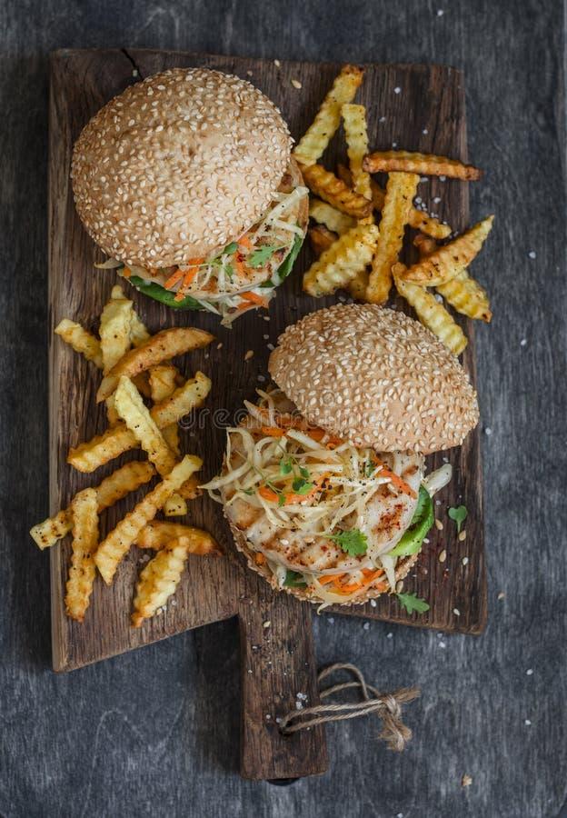 Hamburger grelhados da galinha e da salada de repolho em uma placa de madeira fotografia de stock royalty free