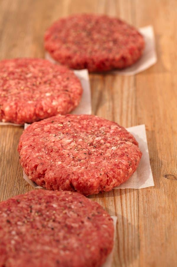 Hamburger grezzi per gli hamburger, sulla tabella di legno immagine stock