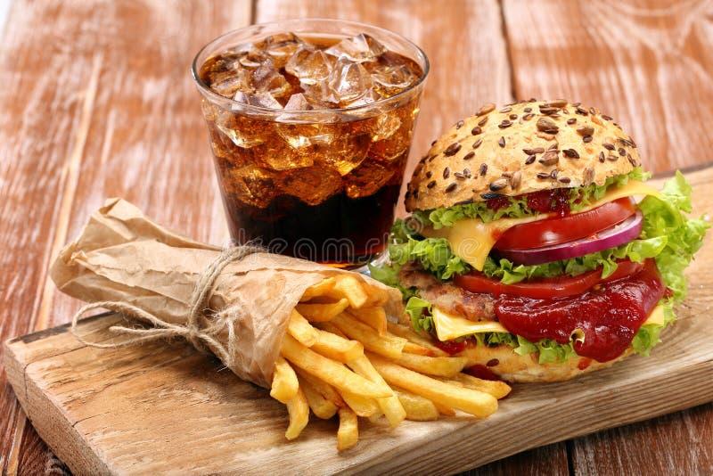 Hamburger grillé avec les fritures et le kola sur le fond en bois image stock
