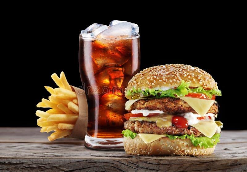 Hamburger, grula dłoniaki, kola napój fotografia royalty free