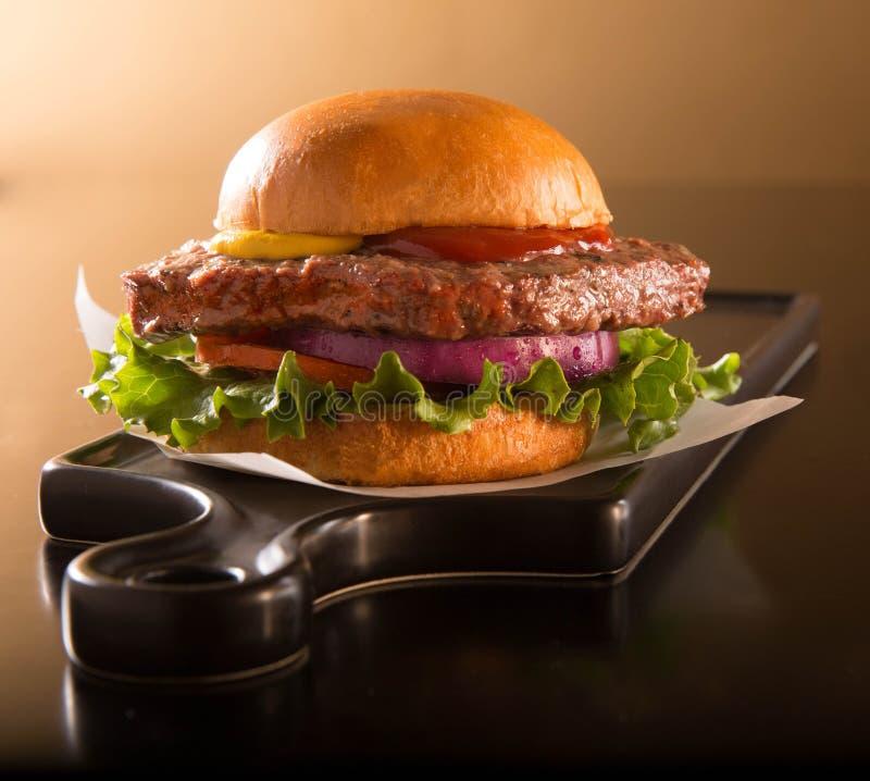 Hamburger on brioche bun on a black plate. Hamburger half pound of beef on a brioche bun on a black plate stock photography