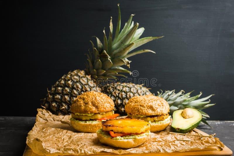 Hamburger hawaïen de vegan avec l'ananas grillé, le guacamole et le paprika grillé photos libres de droits