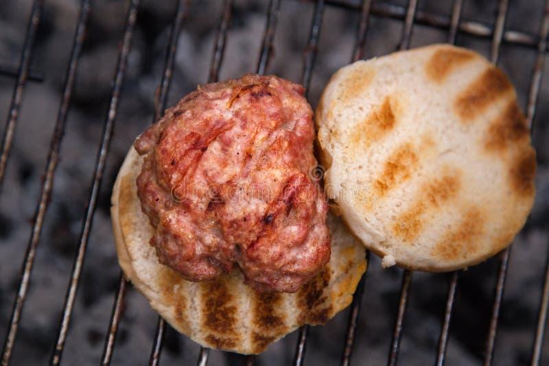 Hamburger i babeczki Piec na grillu na ogieniu Domowej roboty hamburgery zdjęcia stock