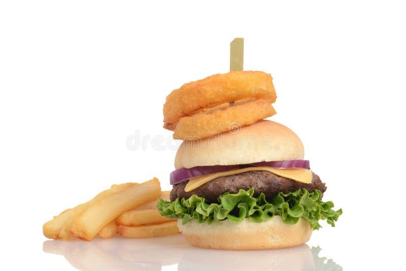 Hamburger i francuz smażymy z cebulkowymi pierścionkami na wierzchołku fotografia royalty free