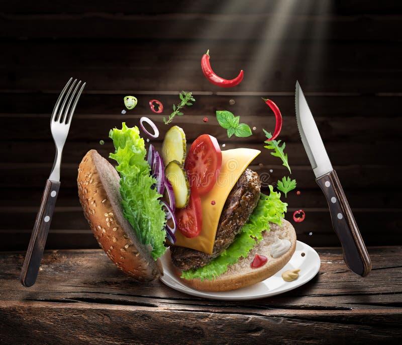 Hamburger-ingrediënten die één voor één vallen om een perfecte maaltijd te maken royalty-vrije stock afbeelding