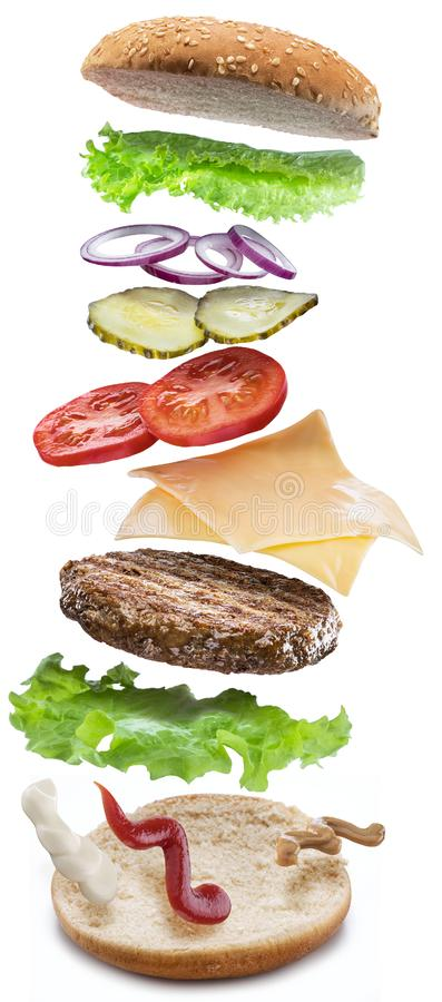 Hamburger ingredients falling down one by one to create a perfect meal. Colorful conceptual picture of burger cooking. Clipping stock photo
