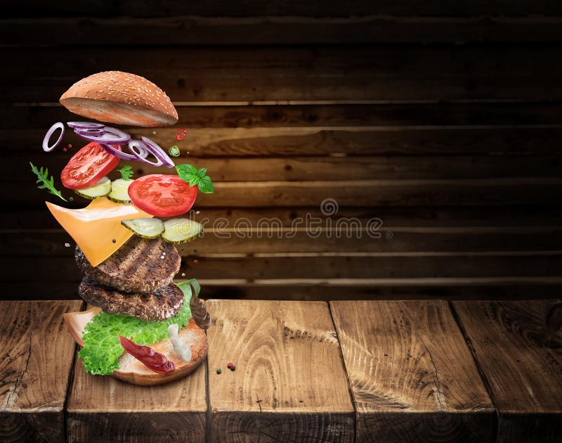 Hamburger ingredients falling down one by one to create a perfect meal. Colorful conceptual picture of burger cooking stock photography