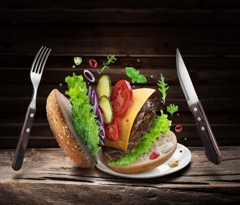 Hamburger ingredients falling down one by one to create a perfect meal. Colorful conceptual picture of burger cooking royalty free stock photography