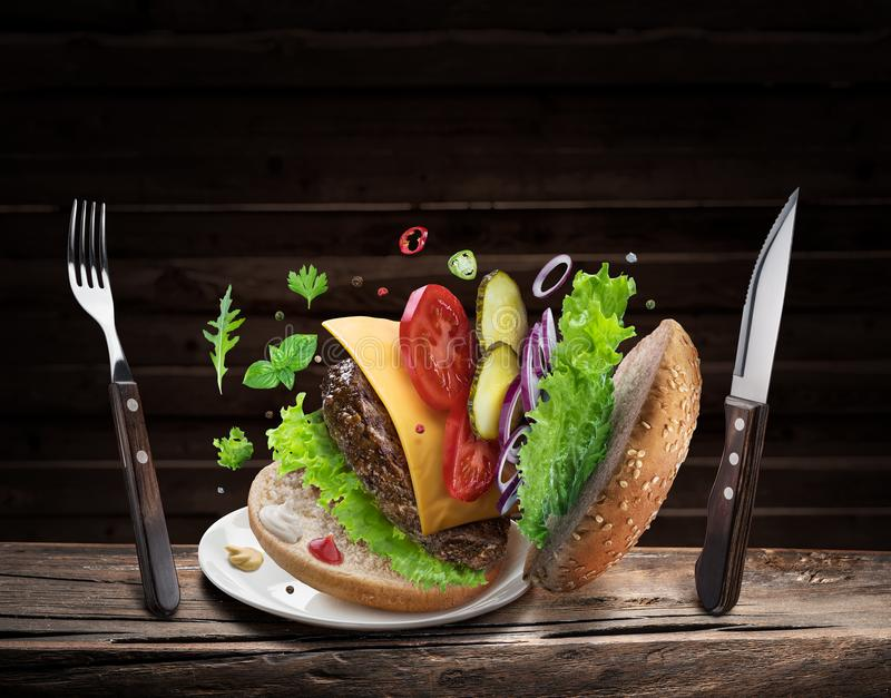 Hamburger ingredients falling down one by one to create a perfect meal. Colorful conceptual picture of burger cooking royalty free stock photos