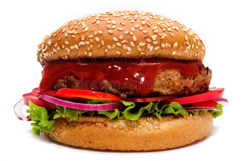 Hamburger juteux avec du boeuf, des tomates, des oignons et la salade sous le ketchup savoureux images stock