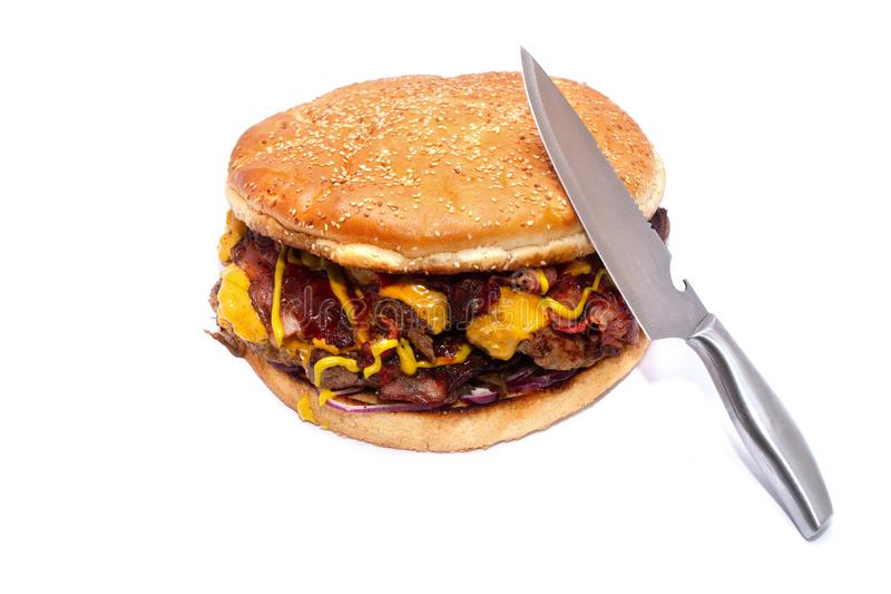 Hamburger juteux d?licieux ?norme avec le lard, les c?telettes de boeuf, la laitue fra?che, les tomates, la sauce, l'oignon, le f image stock
