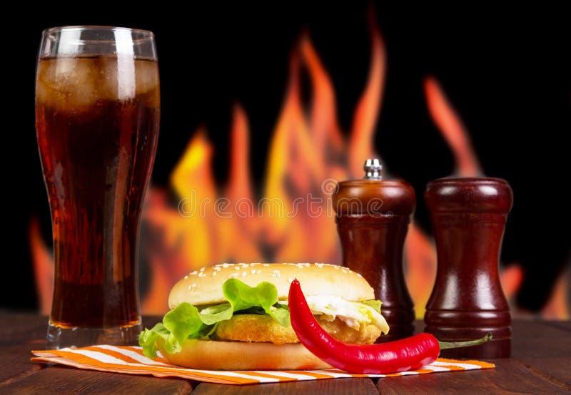 Hamburger, kola, Spaanse pepers en kruiden op achtergrond van vlammen royalty-vrije stock afbeelding