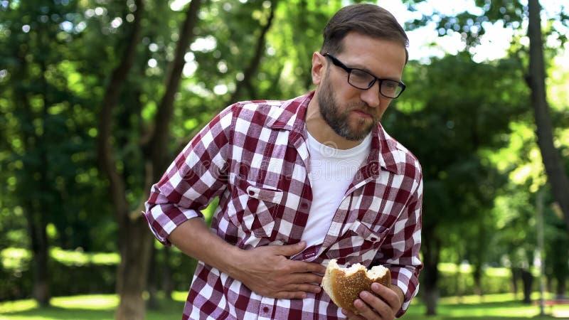 Hamburger masculin de consommation, nausée de sentiment, empoisonnement de nourriture industrielle, intoxication de corps photos libres de droits