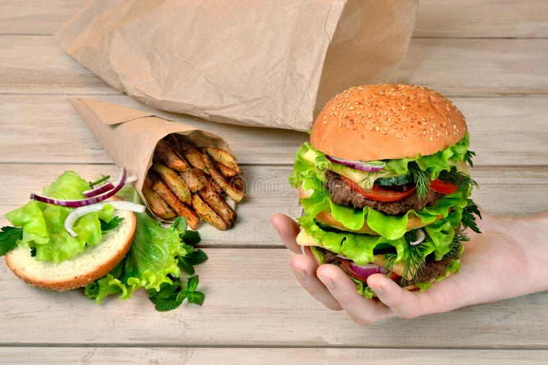 Hamburger in mensen` s hand en frieten op een houten lijst stock afbeeldingen
