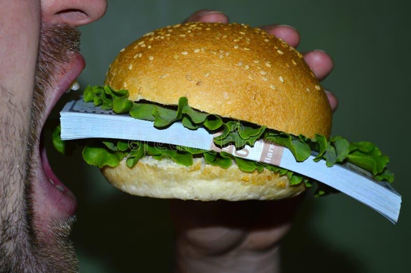 Hamburger met een bos van dollars en een salade gebeten een mens stock afbeeldingen