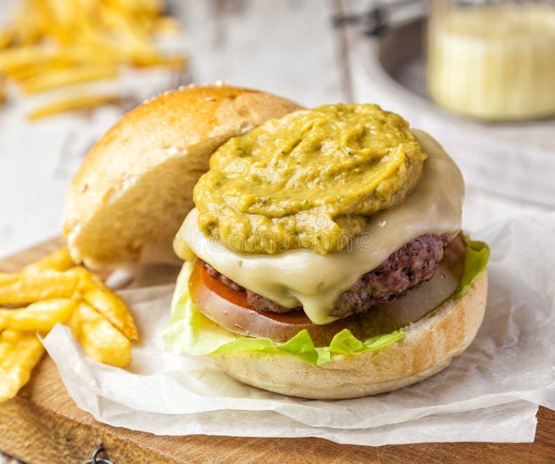 Hamburger met een bovenste laagje van guacamole en eigengemaakte frieten wordt gediend die stock afbeeldingen